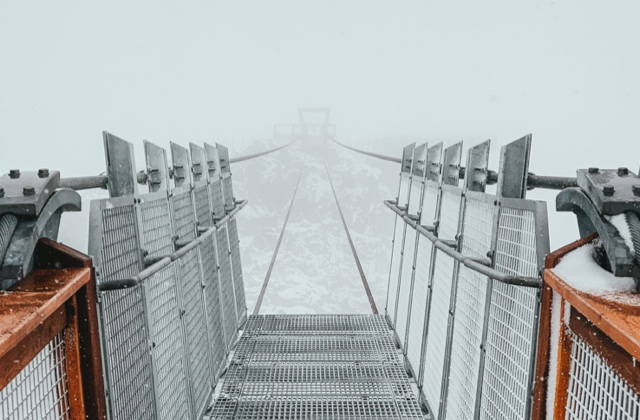 A very scary bridge across a chasm in the mist
